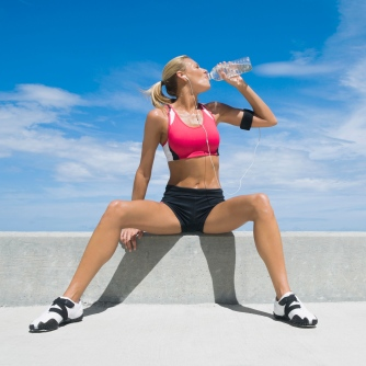 Mid adult woman, drinking water from a water bottle --- Image by © Glowimages/Corbis